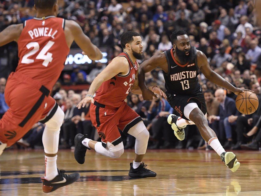 Houston Rockets guard James Harden (13) drives past Toronto Raptors guard Fred VanVleet (23) as Raptors guard Norman Powell (24) moves in during second half NBA action in Toronto.