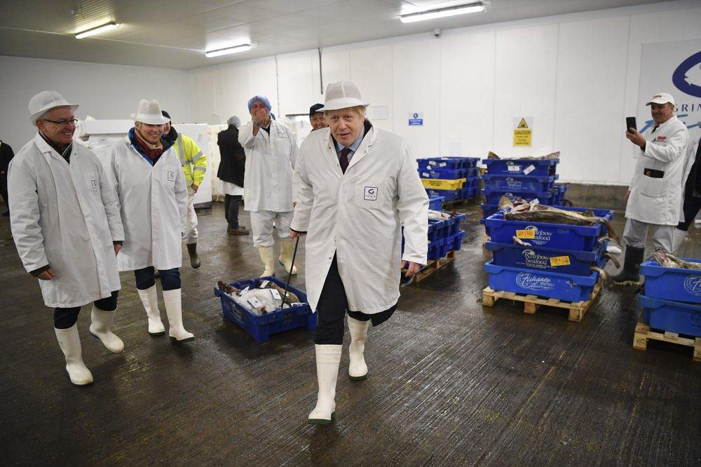 Boris Johnson, center, visits Grimsby fish market in Grimsby, northeast England, yesterday.