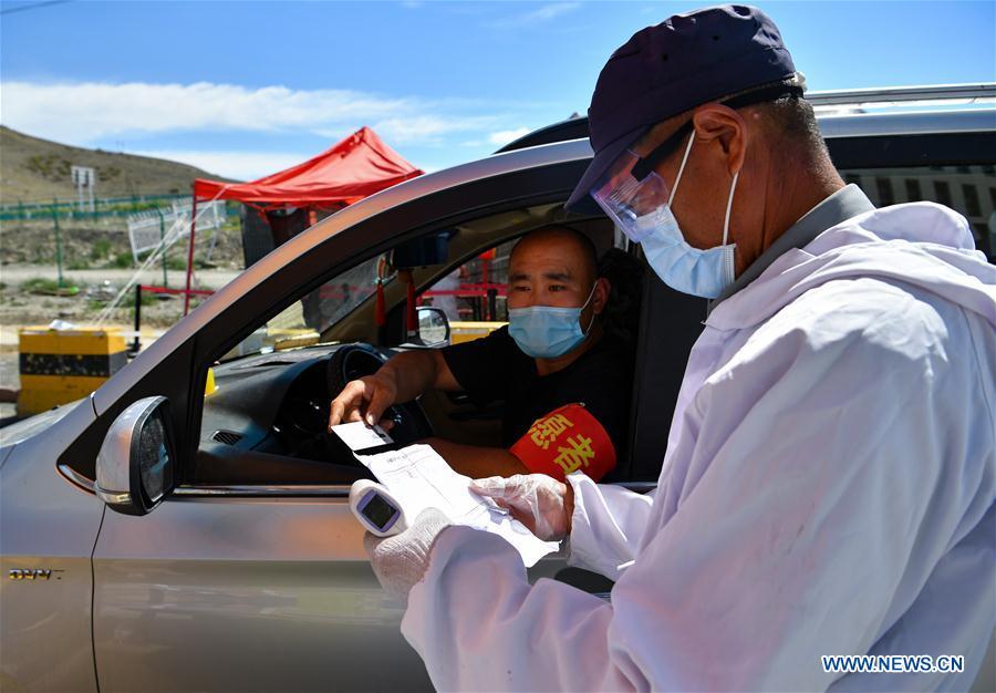 A stafferchecks the information of a man entering the Xinjiang Jiuding farm produce wholesale market at the entrance to the market in Urumqi, Xinjiang on, July 29.