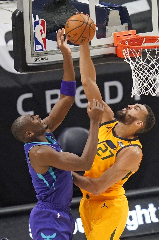 Utah Jazz center Rudy Gobert (27) blocks the shot from Charlotte Hornets center Bismack Biyombo, left, in the first half during an NBA basketball game Monday.