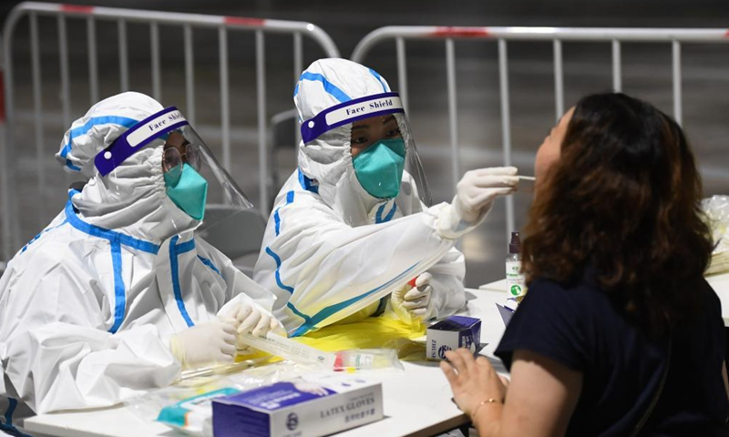 A medical worker takes a swab sample from a woman for a coronavirus disease test in Nanjing, east China's Jiangsu province, July 21, 2021.