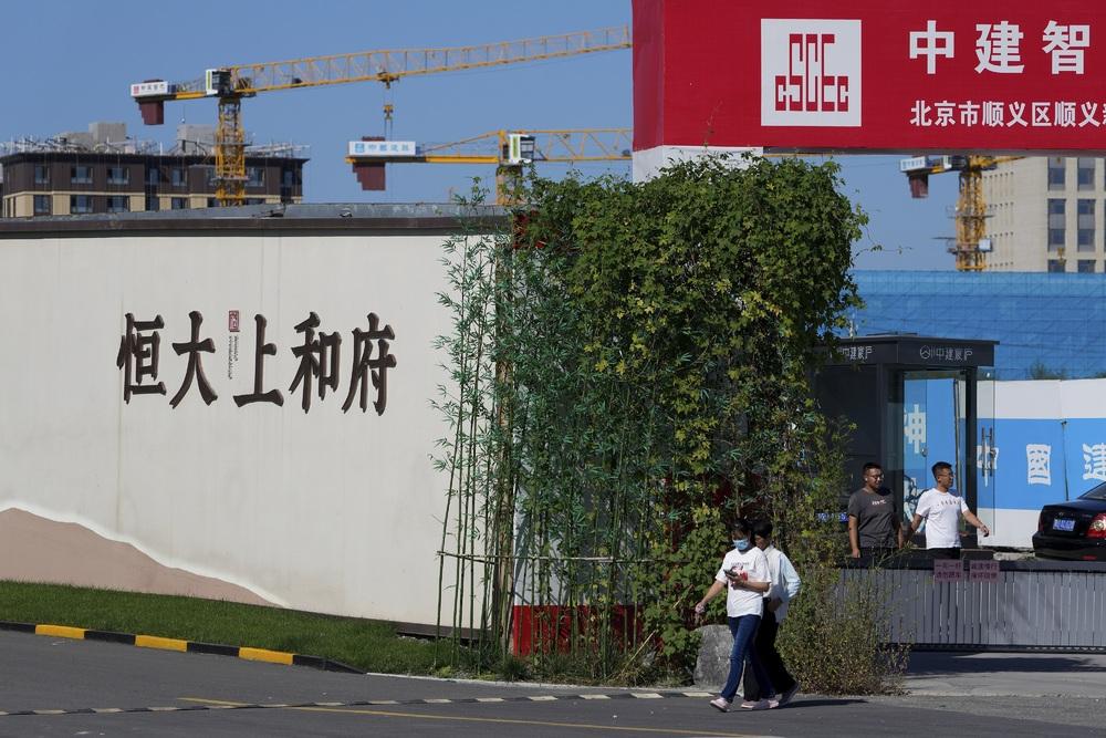 People walk out from an Evergrande new housing development in Beijing. (AP)