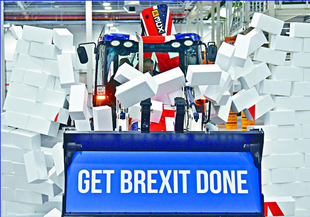 Boris Johnson drives a digger through a symbolic wall carrying the Conservatives' slogan. AP