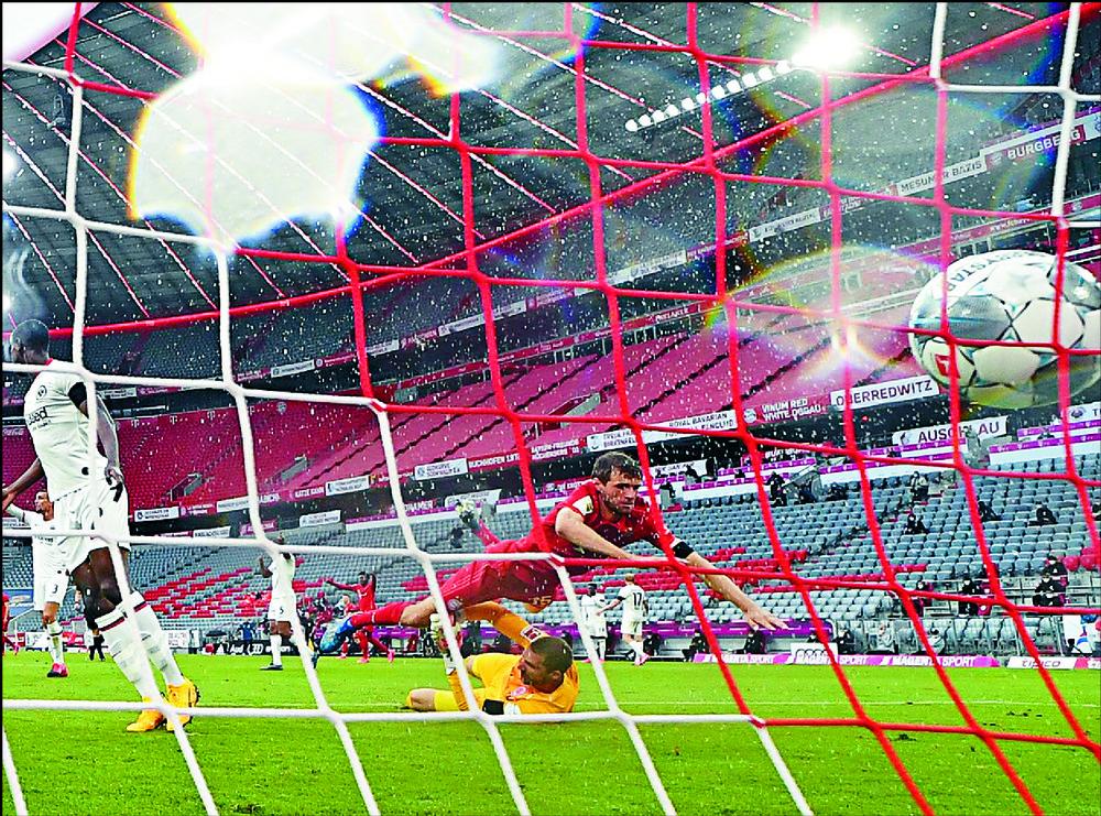 Thomas Muller scores Bayern Munich's second goal during the 5-2 win over Eintracht Frankfurt.  AFP