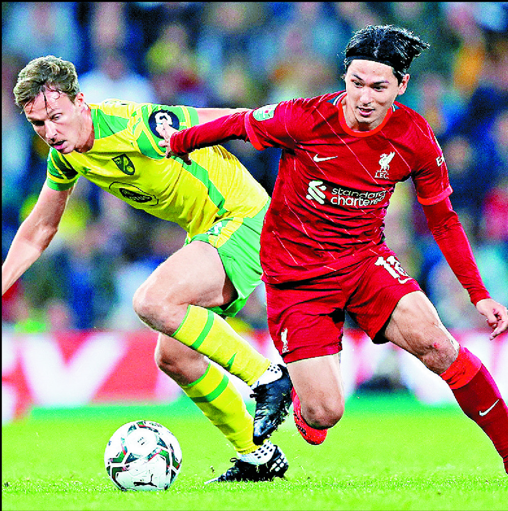 Takumi Minamino, who scored two goals, vies with Kieran Dowell. AFP